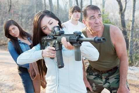 Ashley aims the paintball gun as Lindsey, Michael and Brent Sr. look on.