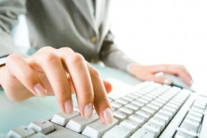 female worker typing at keyboard fingers