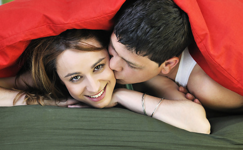 couple kissing under blankets