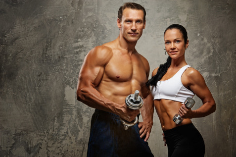 man and women showing off their bodies holding dumbells
